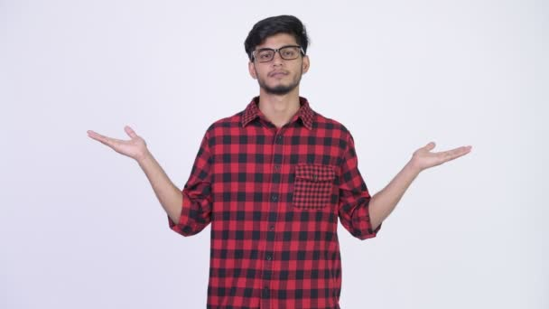Young handsome bearded Indian hipster man comparing something