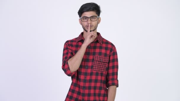 Young happy bearded Indian hipster man with finger on lips