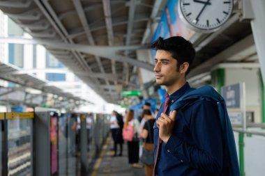 Young handsome Persian businessman exploring the city of Bangkok
