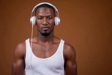 Handsome muscular African man listening to music against brown b