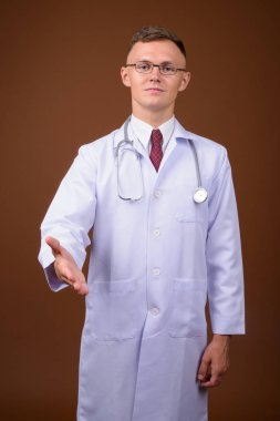 Young man doctor wearing eyeglasses against brown background