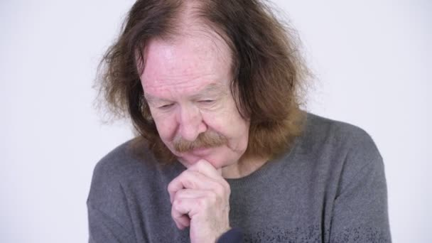 Serious senior man thinking while looking down