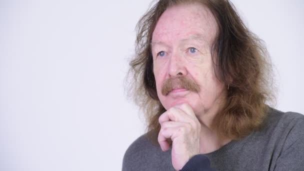 glücklicher älterer Herr mit Schnurrbart, der vor weißem Hintergrund denkt