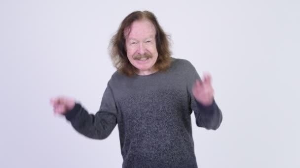 glücklicher Senior mit Schnurrbart drückt Daumen und wünscht