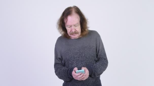 Šťastný starší muž s knírkem, používání telefonu a myšlení