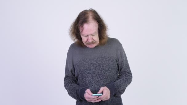 Stressed senior man with mustache using phone and getting bad news