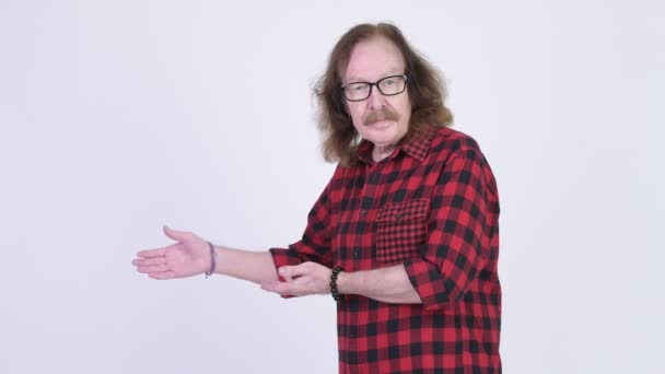 Happy senior hipster man with eyeglasses smiling while showing something