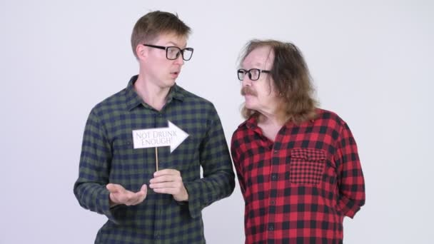 Frustrated senior hipster man and young hipster man showing paper sign together