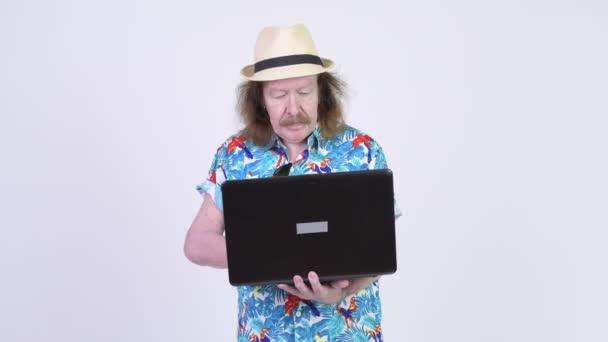 Glücklich senior Tourist Mann lächelnd während mit laptop