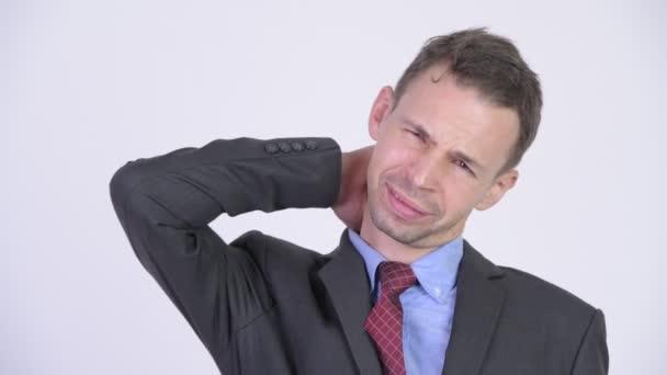 Studio shot of stressed businessman having neck pain