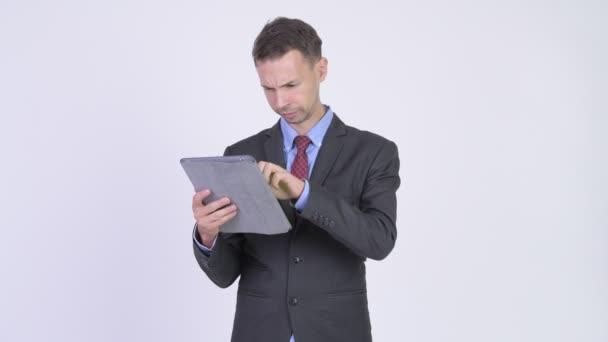 Studio shot of happy businessman using digital tablet and getting good news