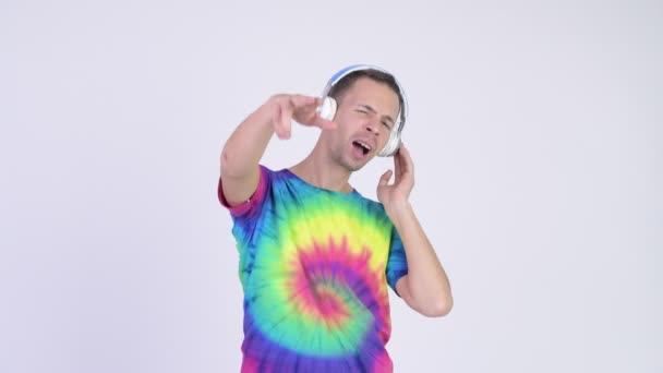 Studio shot of man with tie-dye shirt wearing headphones as DJ