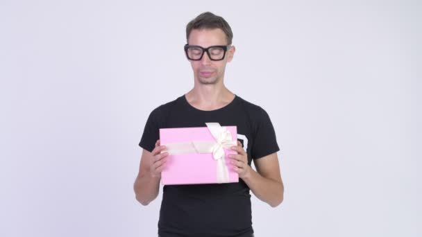 Studio shot of happy nerd man holding gift box