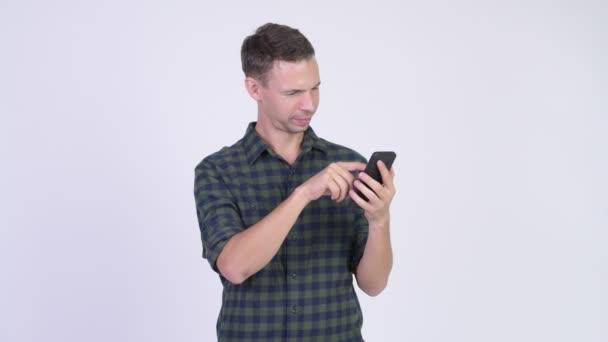 Studio shot of happy hipster man using phone