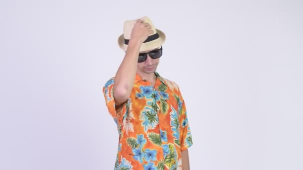 Studio shot of tourist man greeting with hat ready for vacation