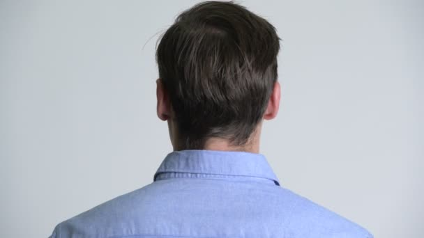 Rear view of young handsome businessman looking back