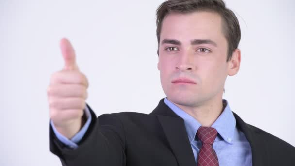 Young happy handsome businessman giving thumbs up