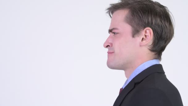 Profile view of young angry businessman shouting