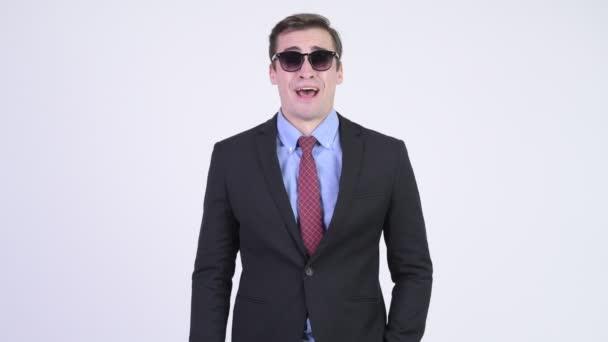 Mladý šťastný pohledný podnikatel odstranění sluneční brýle a směje se