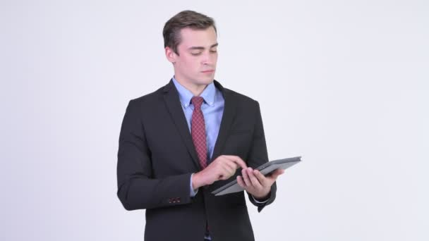 Young happy handsome businessman thinking while using digital tablet