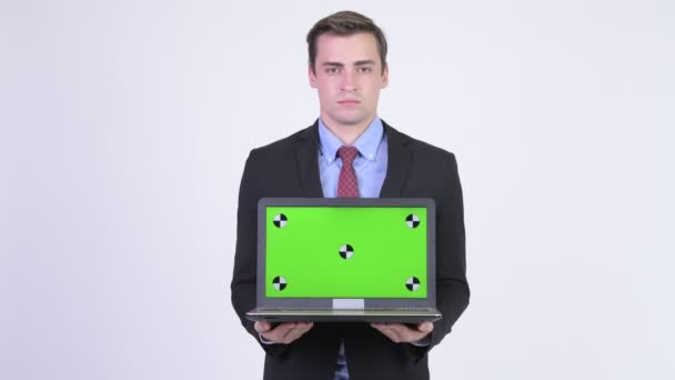Young happy handsome businessman showing laptop