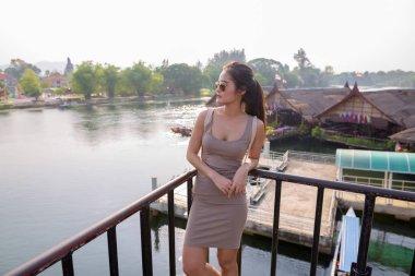 Young beautiful Asian tourist woman outdoors at River Kwai Bridge