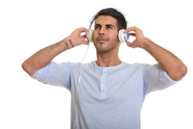 Young happy Persian man smiling while listening to music