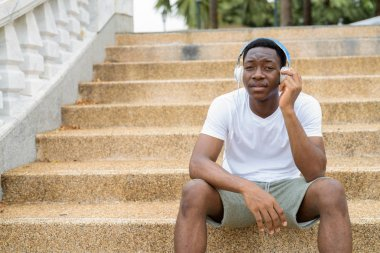 Young handsome African man sitting on stairs while listening music with headphones