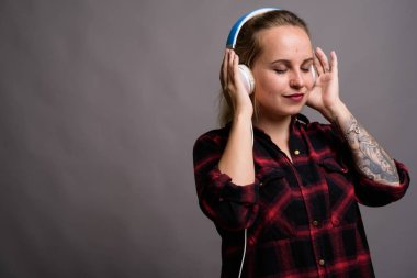 Young beautiful woman with blond hair listening to music against