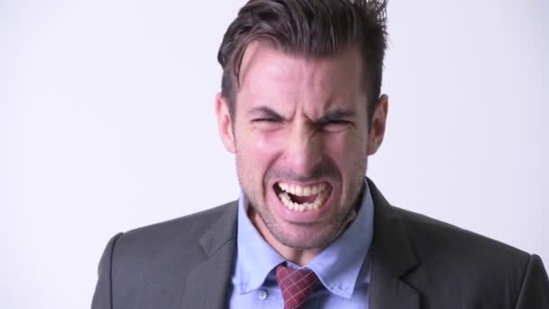 Head shot of young angry Hispanic businessman screaming