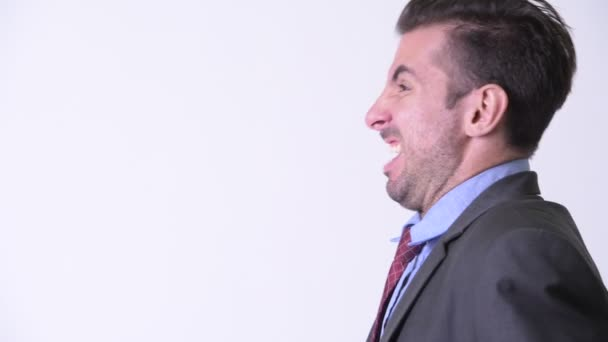 Head shot profile view of young angry Hispanic businessman screaming
