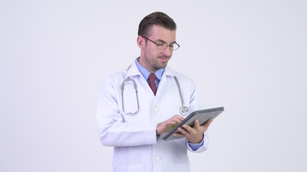 Young happy Hispanic man doctor using digital tablet