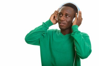 African man listening to music with headphones while thinking