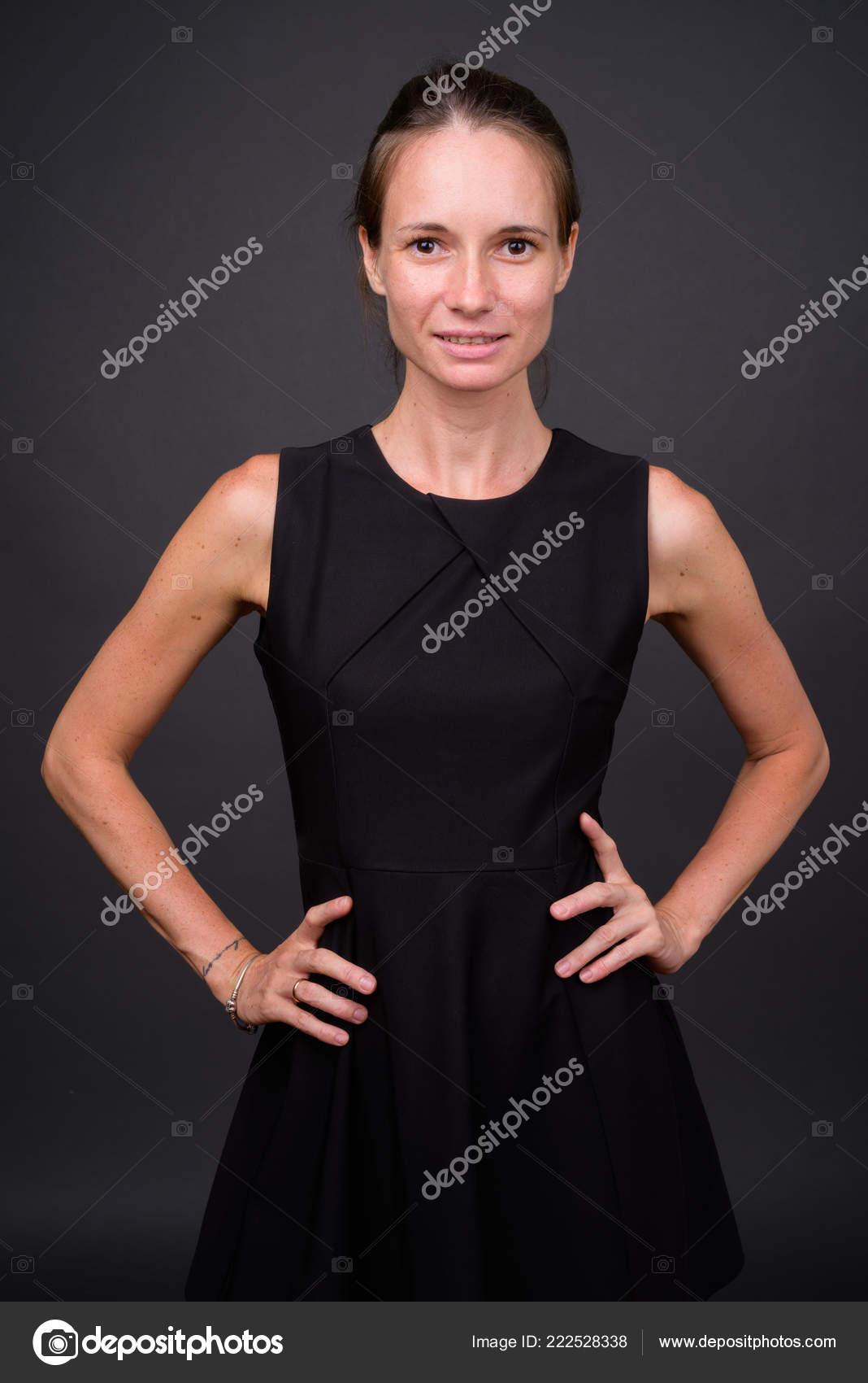 18a2ed8e8b8 Studio shot of beautiful woman wearing black sleeveless dress against gray  background — Photo by amazingmikael