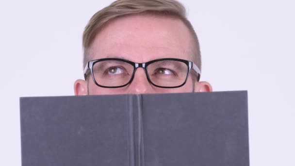 Eyes of blonde hipster man with eyeglasses covering face with book