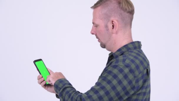 Profile view of blonde hipster man using phone