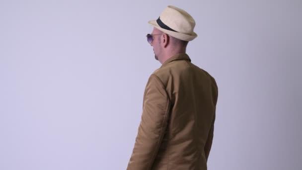 Vista posteriore della biondo casual uomo daffari con il cappello e occhiali da sole guardando indietro