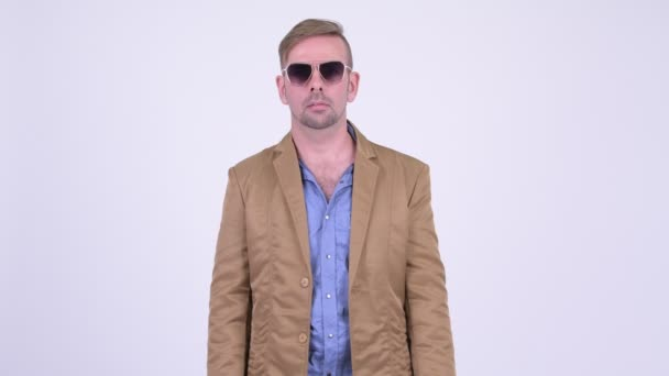 Blonde casual businessman removing sunglasses and looking shocked