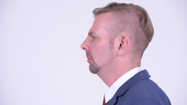 Head shot profile view of angry blonde businessman shouting