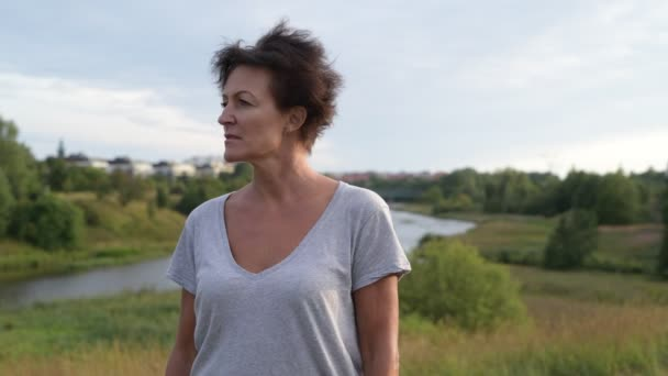 Happy mature beautiful woman thinking against relaxing view of nature