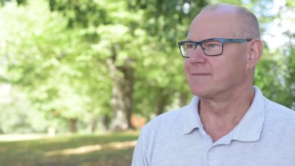 Šťastný starší muž s úsměvem při myšlení v parku