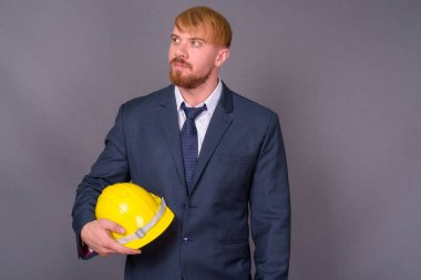 Bearded businessman with hardhat against gray background