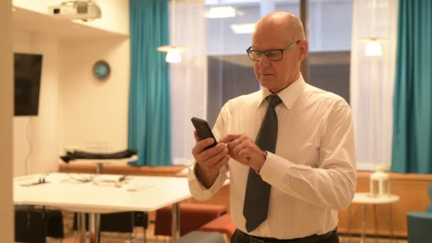Happy Senior Businessman Smiling While Using Phone In The Office