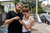 Young couple using mobile phone together in the old playground