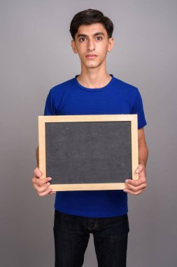 Young handsome Persian teenage boy holding empty blackboard with copy space