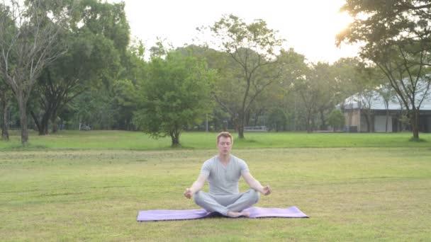 Boldog fiatalember meditál a parkban csukott szemmel