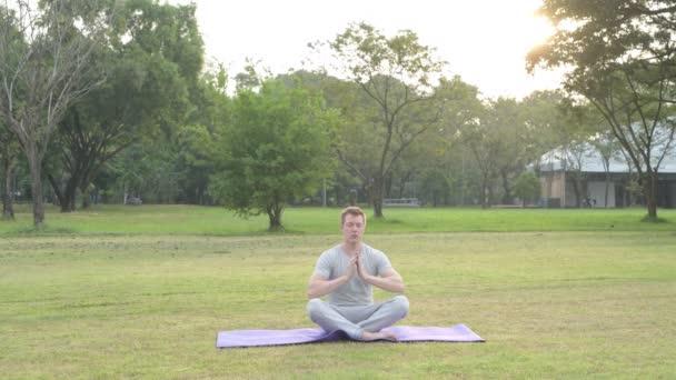 Mladý pohledný muž meditovat se zavřenýma v parku očima