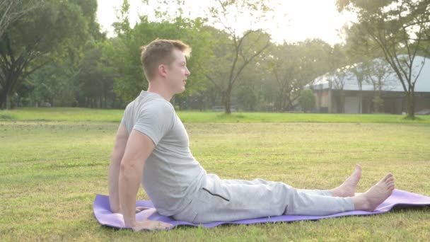 Profile view of young man doing yoga while sitting at the park