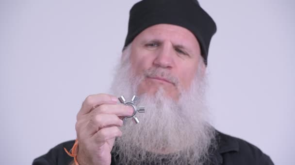 Face of mature bearded hipster man playing with fidget spinner