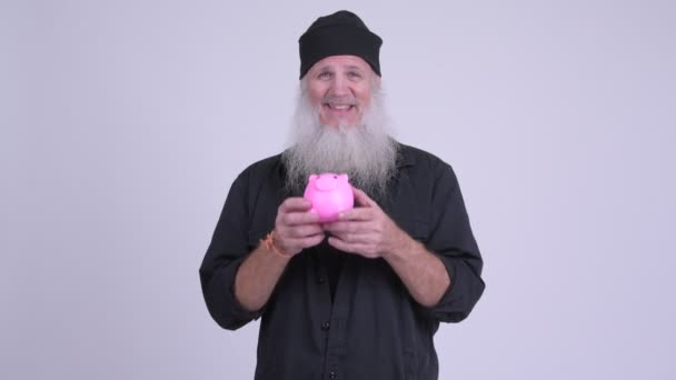 Boldog, érett, szakállas csípő ember giving malacka bank